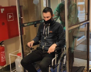 Bramka do dezynfekcji SILVERGATE zamontowana w DPS. Osoba na wózku inwalidzkim z opiekunem przejeżdżają przez bramkę.