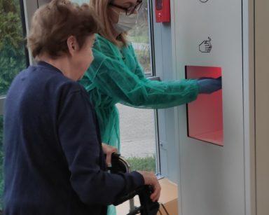 Przy stacji do dezynfekcji rąk stoją dwie kobiety