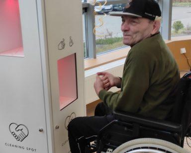 Mężczyzna na wózku inwalidzkim przy stacji do dezynfekcji rąk
