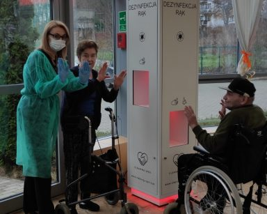 Trzy osoby przy stacji do dezynfekcji rąk
