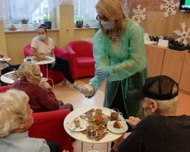 Seniorzy siedzą w fotelach przy stolikach. Dyrektor Agnieszka Cysewska pokazuje srebrną bombkę z napisem Miłość, którą zrobiły dzieci z przedszkola Lokomotywa