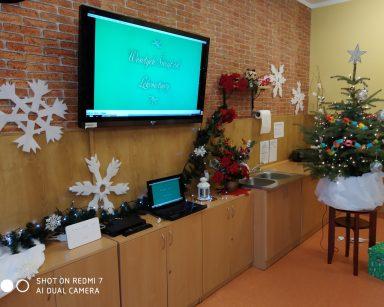 Dekoracje w świetlicy: choinka ozdobiona kolorowym łańcuchem i srebrną gwiazda na czubku. Na ścianie białe śnieżynki, na szafkach poustawiane bukiety czerwonych kwiatów