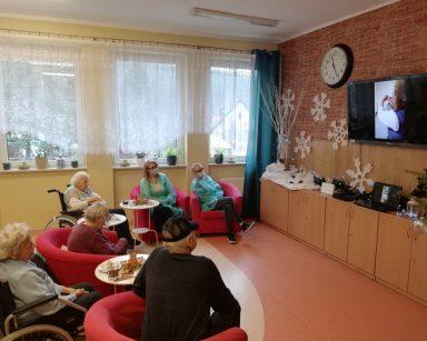 Grupa seniorów i pracowników siedzi w fotelach i ogląda film przygotowany przez dzieci z przedszkola Lokomotywa z życzeniami świątecznymi i kolędami
