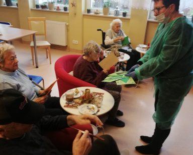 Kierownik Mariola Ludwicka rozdaje seniorom kartki świąteczne przygotowane przez przedszkolaki