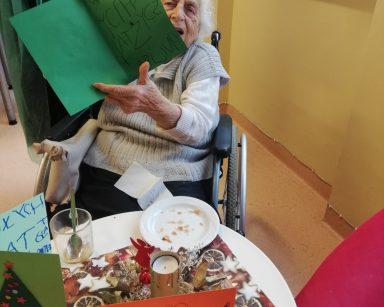 Mieszkanka Pani Krystyna prezentuje zieloną kartkę świąteczną