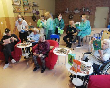 Na pierwszym planie mieszkańcy oglądają świąteczne kartki, z tyłu pracownicy rozdają kartki seniorom