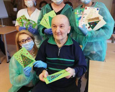 Mieszkaniec pan Piotr trzyma kartkę świąteczną z kolorową choinką, obok niego stoją pracownicy i prezentują zielone i białe kartki świąteczne
