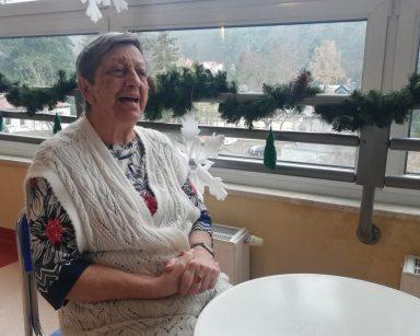 Mieszkanka Pani Alicja siedzi przy białym stoliku, śpiewa kolędy. Za nią okno udekorowane zielonym łańcuchem z gałązek świerku