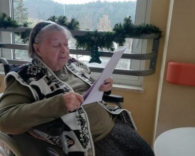 Mieszkanka pani Zofia siedzi przy białym stoliku. Za nią okno udekorowane zielonym łańcuchem z gałązek świerku