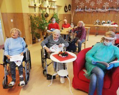 W świetlicy dwie seniorki siedzą na wózkach inwalidzkich, obok kierownik Ilona Gajewska siedzi i czyta śpiewnik z kolędami. Z tyłu seniorzy siedzą przy stołach, trzymają śpiewniki
