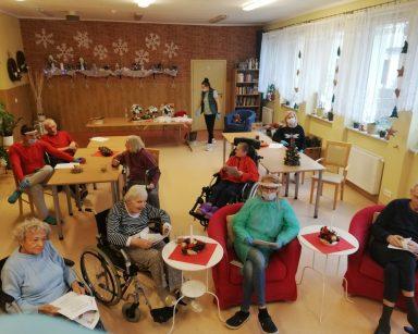 W świetlicy grupa seniorów siedzi na wózkach inwalidzkich, fotelach, przy stołach. Śpiewają kolędy. Sala udekorowana świątecznie: na ścianach białe śnieżynki, na oknach łańcuchy z choinkami i gwiazdami z materiału, na stołach czerwone serwetki i świąteczne świeczniki