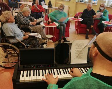 Zdjęcie muzyka pana Arkadiusza oraz klawiatury pianina, na którym gra. Na pianinie oparty śpiewnik. Z tyłu grupa seniorów i pracowników śpiewa kolędy