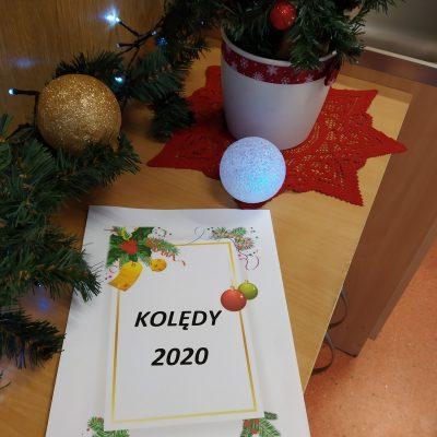 Zdjęcie śpiewnika: biała okładka ze złota ramką i świąteczne dekoracje