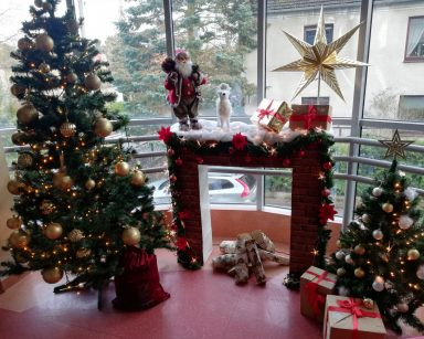 Kominek przystrojony figurką Mikołaja, renifera i prezentami zapakowanymi w świąteczny papier, obok choinka z bombkami, dekoracja na poziomie 0