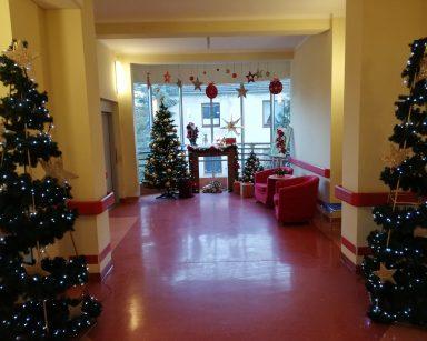 Zdjęcie korytarza z dekoracjami świątecznymi na poziomie 0: pod ścianami dwie choinki ustrojone w złote światełka, za nimi kominek, dwie choinki z bombkami i dwa czerwone fotele