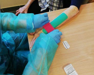Fizjoterapeutka Martyna Józefczyk w trakcie naklejania taśm na rękę seniorki