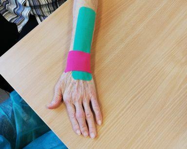 Przedramię seniorki z naklejonymi taśmami kinezjologicznymi wspomagającymi pracę mięśni