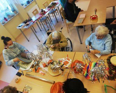 Terapeutka Magdalena Poraj-Górska z seniorkami siedzą przy stole pełnym błyszczących dekoracji noworocznych i przygotowują maski