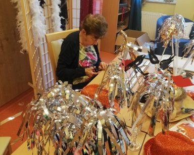 Seniorka siedzi przy stole z noworocznymi ozdobami