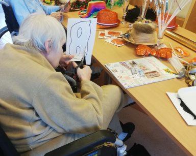 Seniorka siedzi przy stole z ozdobami noworocznymi i wycina papierową maskę, za nią siedzi druga seniorka