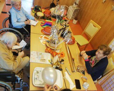 Trzy seniorki z terapeutką Magdą Poraj-Górską siedzą przy stole z ozdobami noworocznymi