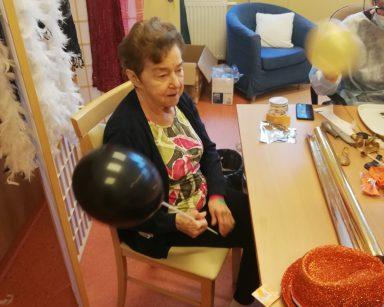 Seniorka siedzi przy stole z czarnym balonem w dłoni
