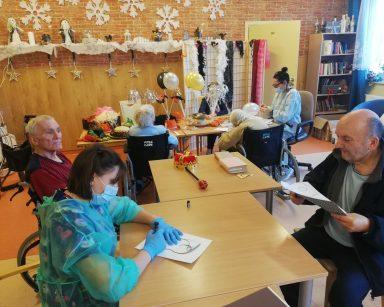 Senior z fizjoterapeutką Martyną Józefczyk siedzą przy stole, wycinają maski. W tle siedzą inni seniorzy i przygotowują ozdoby noworoczne