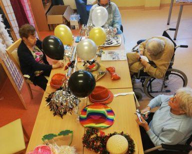 Widok z góry: trzy seniorki z terapeutką Magdą Poraj- Górską siedzą przy stole i przygotowują ozdoby noworoczne