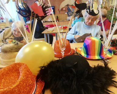 Na pierwszym planie kolorowe, noworoczne kapelusze z piór i brokatu, maski na patykach. Na drugim planie seniorki przygotowujące ozdoby noworoczne