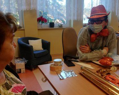 Terapeutka Magda Poraj-Górska w kapeluszu z pomarańczowego brokatu i pomarańczową muszką na szyi z seniorką przy stole.
