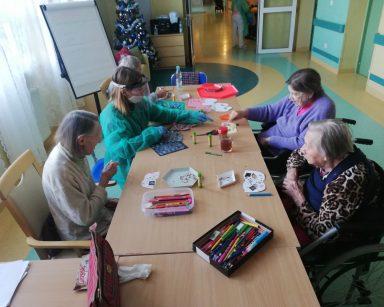Widok z góry: psycholożka Maria Skubich-Wiczling przy stole z seniorkami przygotowują maski noworoczne