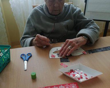 Seniorka przygotowuje maskę noworoczną z papieru