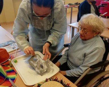 Terapeutka Magda Poraj-Górska z seniorką obsypują papierową maskę srebrnym brokatem