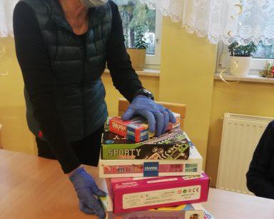 Terapeutka Magda Poraj-Górska trzyma w rękach pudełka z grami planszowymi