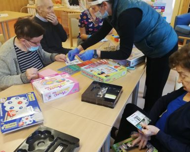 Terapeutka Magda Poraj-Górska i seniorzy siedzący przy stołach rozkładają gry planszowe