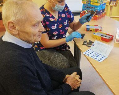 Fizjoterapeutka Martyna Józefczyk siedzi przy stole z seniorem i rozkłada grę