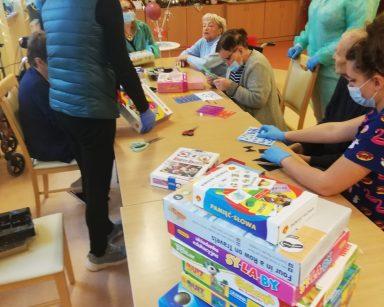 Na pierwszym planie stos pudełek z grami planszowymi, w tle seniorzy przy stole rozkładają gry.