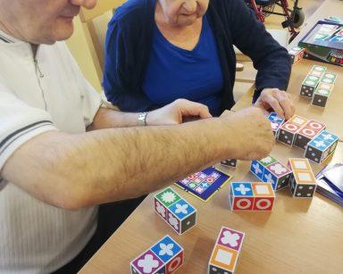 Seniorzy przy stole grają w