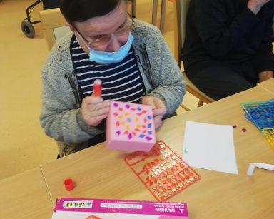 Seniorka dekoruje pudełko ozdobami z gry
