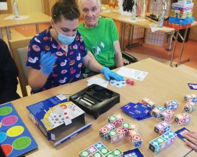 Fizjoterapeutka Martyna Józefczyk gra z seniorem w grę