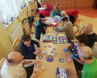 Widok z góry na grupę seniorów i pracowników DPS grających w gry planszowe