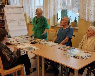 Terapeutka Ewa Rodziewicz z seniorem przeglądają prasę filmową