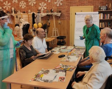 Terapeutka Ewa Rodziewicz rozmawia z grupą seniorów siedzących przy stole