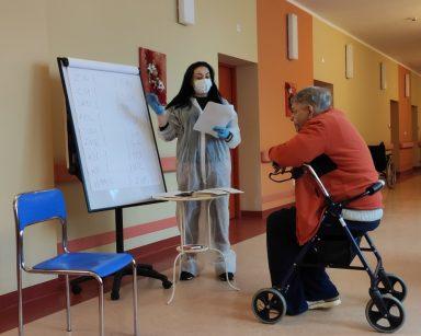 Terapeutka Gosia Jancelewicz z seniorem przy tablicy flipchart w trakcie zajęć