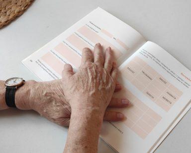 Dłonie seniorki na otwartej książce
