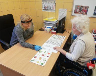 Neurologopeda Anna Szmaja-Wysocka i seniorka siedzą przy stole, na blacie rozłożone tablice do komunikacji alternatywnej