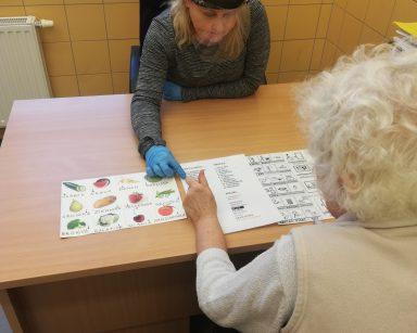 Seniorka rozmawia z neurologopedą przy pomocy tablic do komunikacji alternatywnej
