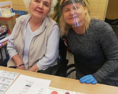 Seniorka i neurologopeda Anna Szmaja-Wysocka siedzą przy stole z tablicami do komunikacji AAC i uśmiechają się