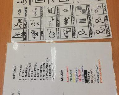 Na stole leżą tablice do komunikacji AAC z symbolami Makatona i zapisanymi wyrazami