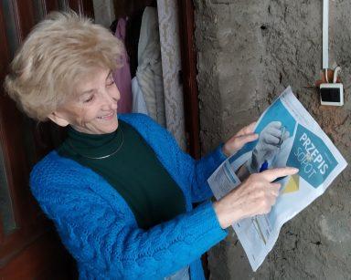 Uśmiechnięta uczestniczka DDP stoi przed drzwiami do domu i trzyma w ręku gazetę Przepis na Sopot, w którym są informacje na temat szczepień